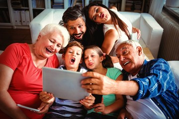 Multi generation family taking a selfie on digital tablet in