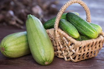Fresh cucumbers in basket and zucchini on wooden background