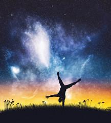Acrobat man standing on one hand on night sky.