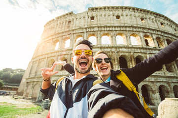 Printed kitchen splashbacks Rome Happy caucasian couple is taking a selfie smiling at the camera in front of the colosseum in Rome