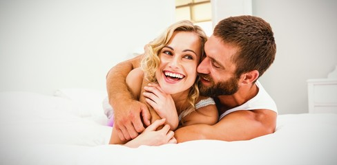 Young couple embracing on bed