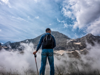 A man stands on a slope and admires the tops of mountains in the clouds.