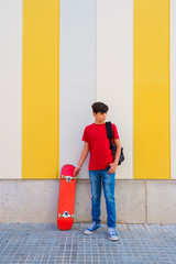 Young boy wearing casual clothes standing against a colored wall holding a skateboard while looking away