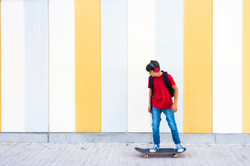 Side view of a young boy wearing casual clothes skateboarding against a colored wall