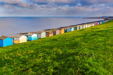 Row of beach huts along the coast in Tankerton, Whitstable, Kent. The green grass slopes are behind the huts and groynes, water breakers can be seen along the beach