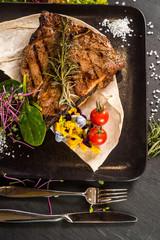 Grilled marble steak dish on black background