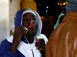 A migrant blows soap bubbles on the migrant search and rescue ship Sea-Watch 3, operated by German NGO Sea-Watch, off the coast of Malta in the central Mediterranean Sea