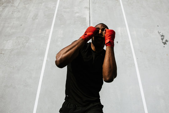 Man in fighting stance against wall