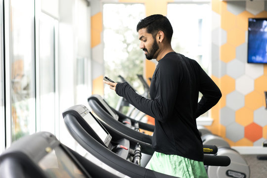 Side view of man exercising on treadmill while using smartphone