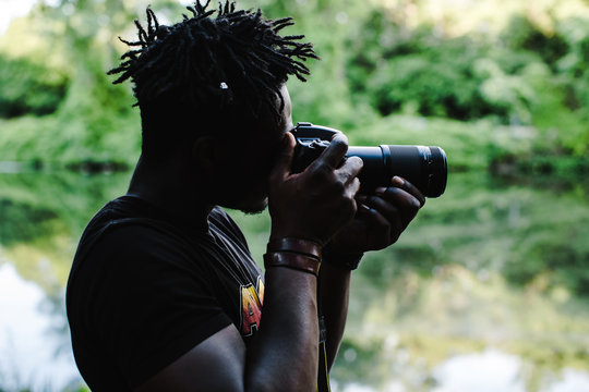 Side view of man taking picture outdoors