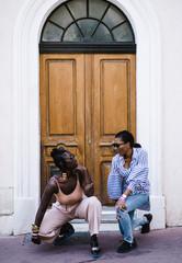 Women posing against door