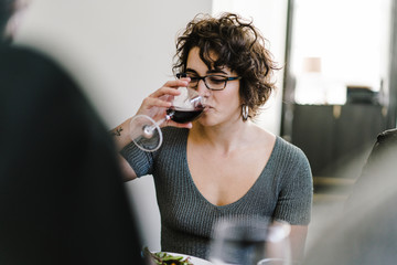 Woman drinking wine while sitting in restaurant