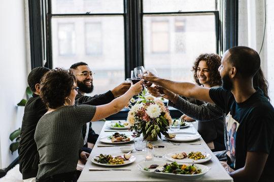 Friends toasting wine glasses  in restaurant