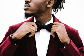 Midsection of young man adjusting bow tie