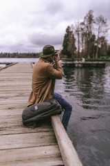 Young man taking picture with camera while sitting on pier