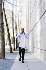 Portrait of man walking on sidewalk