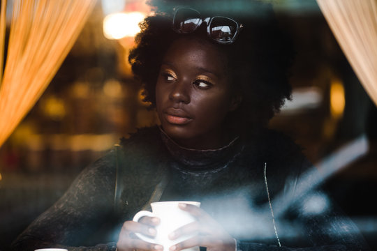 Girl drinking coffee while sitting in cafe