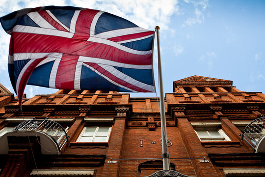 A british flag flies high above the streets of london.