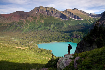 Silhouette of a man standing on a ridge looking over Lower Grinnell Lake in Glacier National Park, Montana.