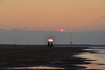 Sylwetki na plaży na tle zachodzącego słońca.