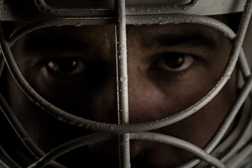 Detail of a male face in a goalie hockey mask.This is a detail hockey goalie. He is concentrated on game.