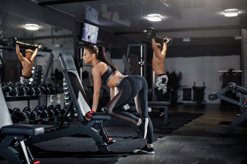 Slender bodybuilder girl and boy lifting a heavy dumbbell, standing in front of the mirror during a workout at the gym. Sport concept, fat burning and healthy lifestyle