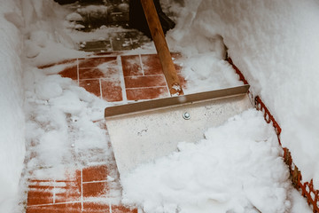 Snow removal with an iron shovel. With a wooden handle. Winter cleaning of the yard from the snow. After a heavy snowfall. Cleaning the steps from red tiles