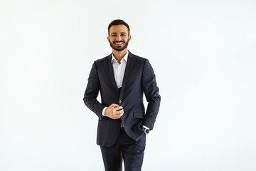 The businessman in a beautiful suit standing on the white background Wall mural