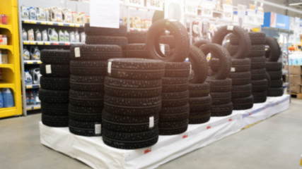 Blurred image of car tires for sale. Photo of lots of car tires in the shop for hot sale. Advertisment for car tires