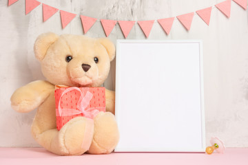 Children's toys, a teddy bear and a frame on a light wall background, for design, layout. Baby shower