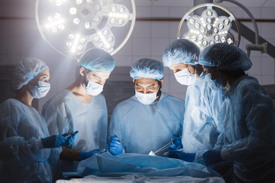 Surgeons team during operation process in surgery in a dark background. Surgeons stand up through 10-,12-,15-hour surgeries without food, without bathroom breaks without complaints.