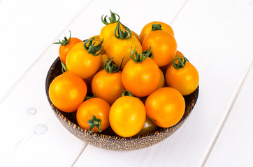 Golden yellow cherry tomatoes in wooden bowl