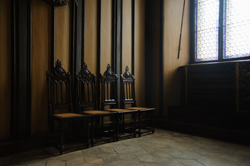 four chairs in a dark room of a castle near the window