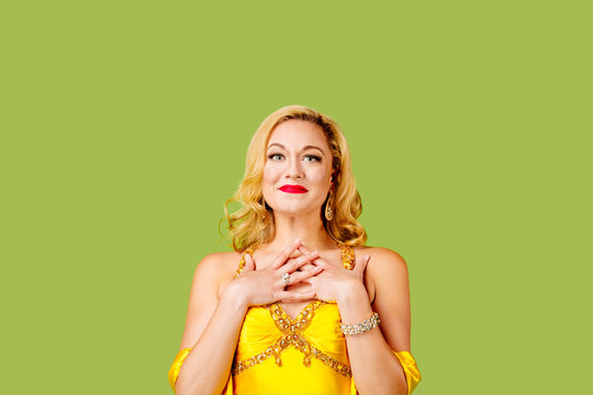 Dressed up blonde woman full of emotion, isolated on green studio background