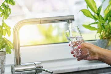 Woman filling glass with water from faucet in kitchen