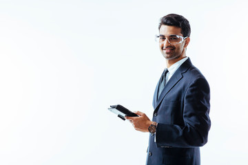 Portrait of man in business suit holding electronic tablet pad and protective glasses looking at camera, isolated on white studio background