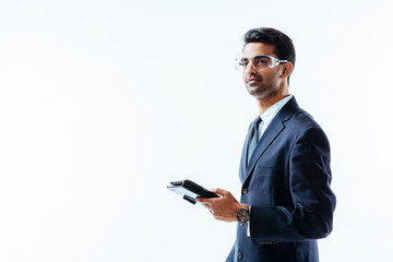 Portrait of man in business suit holding electronic tablet pad and protective glasses looking upwards,  isolated on white studio background