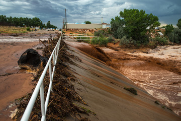 Muddy flash flood running through culverts in rural desert town