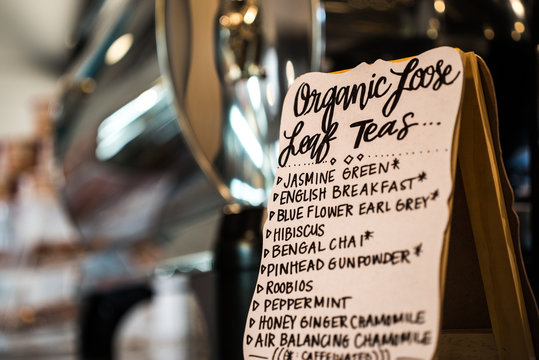 """Organic Loose leaf teas"" sign in front of espresso machine in cafe"