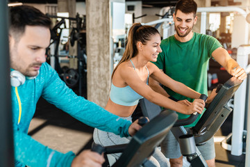 Happy caucasian female athlete practicing on exercise bike with personal trainer in the gym