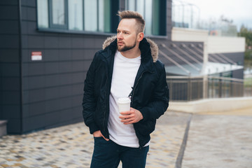 Attractive young man in casual clothers with coffee in his hands standing on office building background.