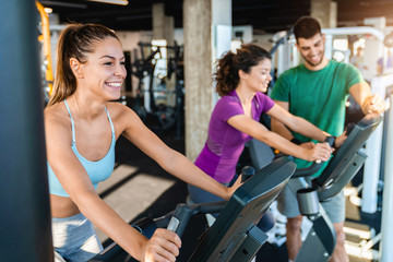 Smiling caucasian female athlete practicing on exercise bike in the gym