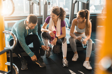 Young athletic friends talking on a break in a health club
