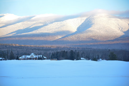 Snowy mountain and house in Vermont at dusk