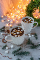 Hot cocoa with marshmallows in white sweater mugs in Christmas setting