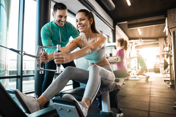 Happy athlete doing rowing workout with personal trainer in the gym Wall mural