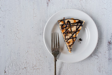 Caramel and chocolate drizzle peanut butter tart pie slice with fork flat lay