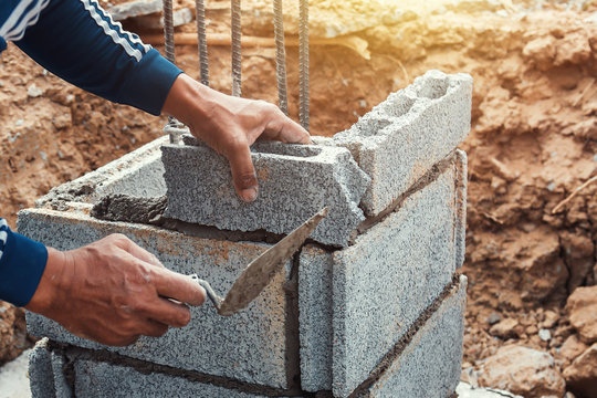 worker installing bricks in construction site