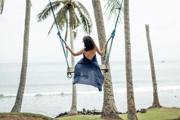 Woman swings on a tropical beach of Bali island, Indonesia.