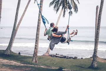 Young couple swinging on the tropical beach of Bali island, Indonesia.